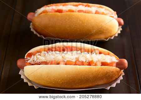 Chilean Completo Clasico (classical) or Completo Aleman (German) traditional hot dog sandwiches made of bread sausage tomato cubes and sauerkraut photographed on dark wood with natural light (Selective Focus Focus in the middle of the first hotdog)