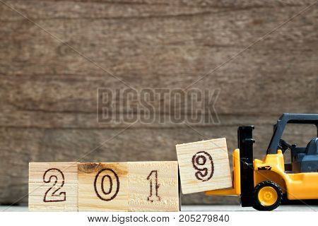Toy plastic forklift hold block to compose and fulfill wording 2019 on wood background