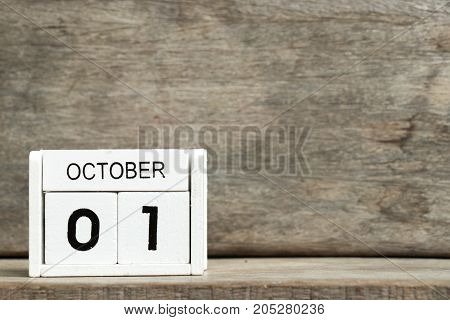 White block calendar present date 1 and month October on wood background
