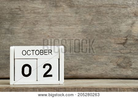White block calendar present date 2 and month October on wood background