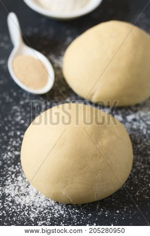 Risen or proved yeast dough balls for bread or pizza on a floured slate surface ingredients in the back photographed with natural light (Selective Focus Focus on the front of the dough ball)