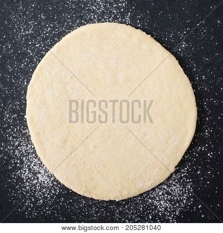Rolled out pizza dough on floured slate surface photographed overhead with natural light