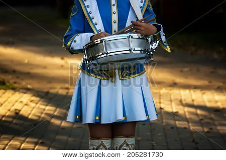 Girl Drummer Holds A Drum And Drum Sticks In Hand At The Parade On The Street.