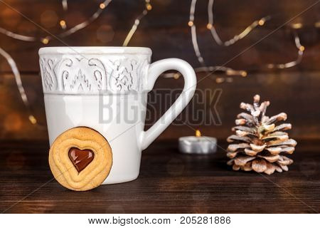 A photo of a cookie with a cup of hot chocolate behind it, with a snowy pine cone, a candle, and fairy lights in the blurred background, with a place for text, side view, on dark textures