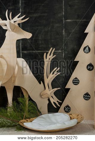 New Year's and Christmas decorations and fir plywood deer and a tree on a dark background