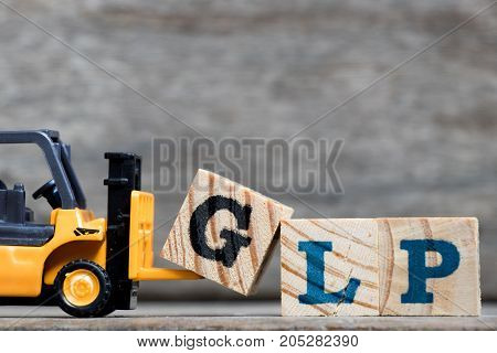 Yellow plastic forklift hold letter G to complete word GLP (Abbreviation Good Laboratory Practicee) on wood background