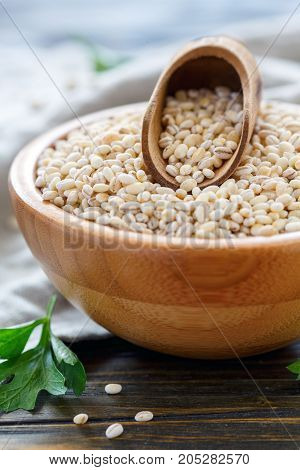 Bowl Of Pearl Barley And Wooden Scoop.