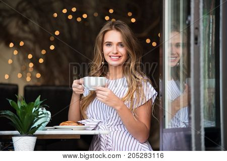 Beautiful happy woman having classic french breakfast with coffee and croissant cake at the cafe