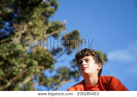 Boy looking ahead pensively while resting on top of wall with sun striking side of face.