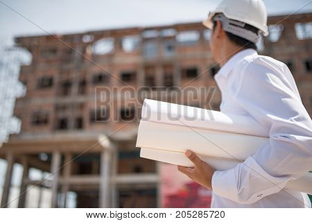 Construction worker checking blueprints on site, Construction manager and engineer working on building site