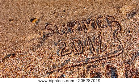 Summer 2018 written on the sea sand beach.Textured sandy template for New year greetings