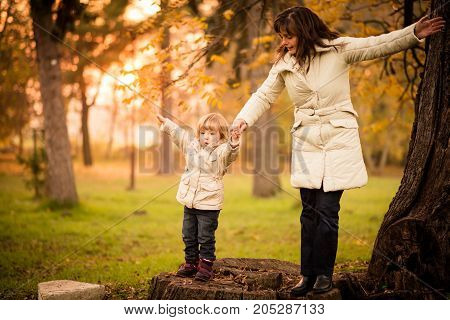 Mother child standing on big stump in evening nature pretending to fly