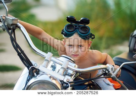 the child sits on his father's motorcycle . The dream of becoming a biker