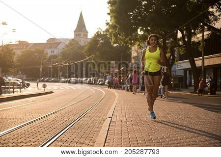 Motivational fitness woman running with determination in street