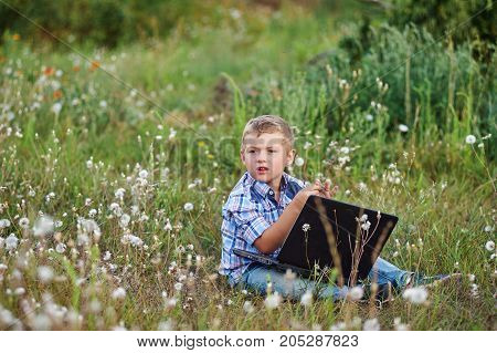the boy sitting in Park with laptop