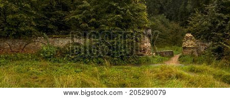 Old fence and destroyed gate from red bricks in forest. Panorama