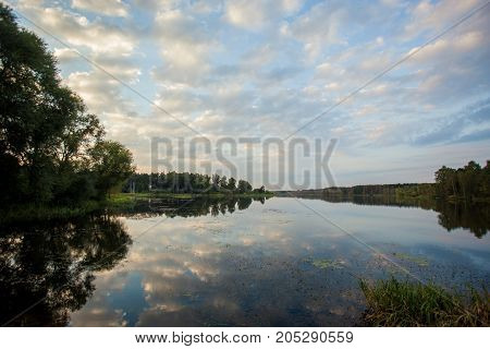 sunset on great lake with the clouds reflected in the water and the forest around