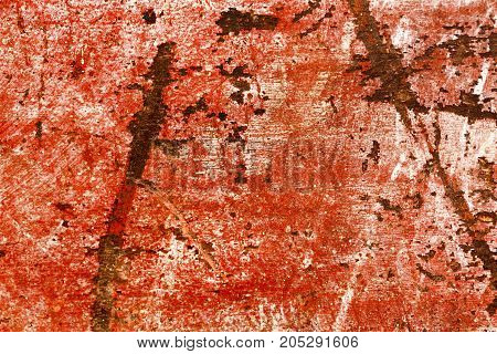 Heavily damaged scratched piece of red painted wood. High resolution photo.