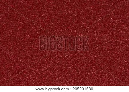 A red paper background with mottled texture. High resolution photo.