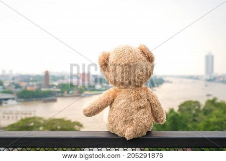 Lonely teddy Bear sitting river view. (Chao Phraya river in Bangkok city)