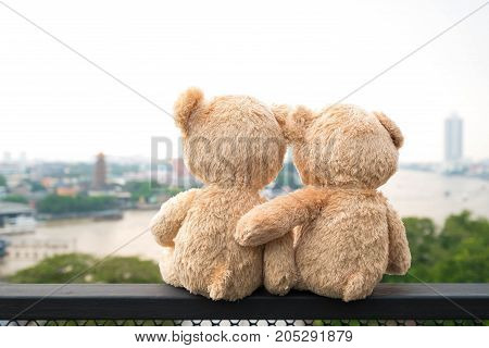 Two teddy bears sitting river view. Love and relationship concept (Chao Phraya river in Bangkok city)