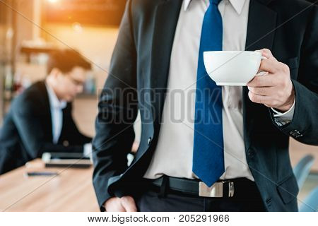 Businessman holding a white coffee cup and drink coffee in the morning. Another businessman working behind him.