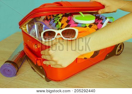 Woman packing stuff into suitcase at home. Travel and vacation concept. Open suitcase with clothes and personal things packed for travelling - Retro color