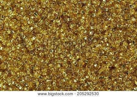 Close up of golden yellow seed beads. High resolution photo.
