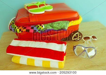 Suitcase with things for spending summer vacation things prepared for travel. red suitcase with clothing on table - Retro color