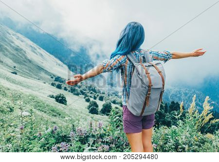 Unrecognizable traveler young woman with backpack standing with raised arms in summer mountains.