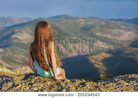 A girl with red hair sits on top of the cliff at the very edge of the abyss, admiring the scenery of the mountains, the rear view. Selective focus