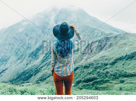 Explorer young woman in a hat standing in front of mountains in summer rear view.