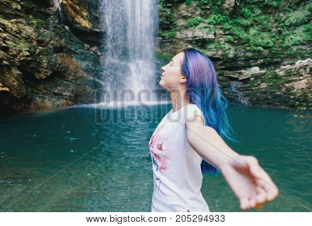 Freedom happy young woman standing with raised arms near the waterfall in summer side view.