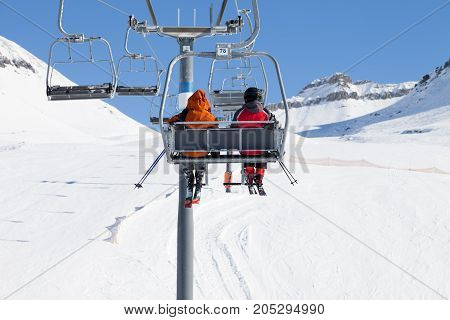 Two skiers go up on chair-lift and snow ski at sun winter day. Caucasus Mountains Georgia region Gudauri.