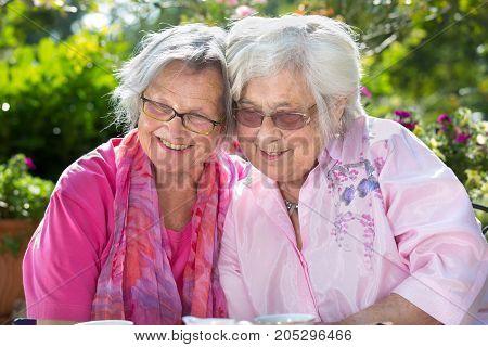 Two Smiling Senior Woman Relaxing In Garden