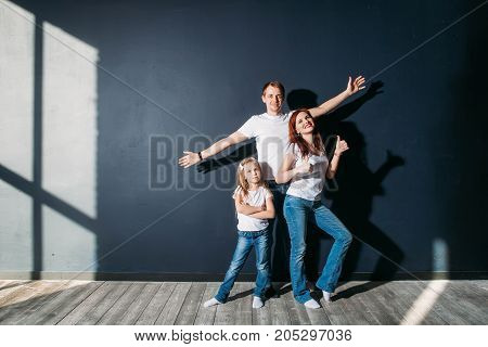 Happy young family portrait standing on gray background wooden floor room window sunny day