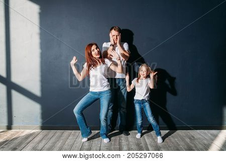Stress young dad standing with happy child and wife on gray background wooden floor room window sunny day