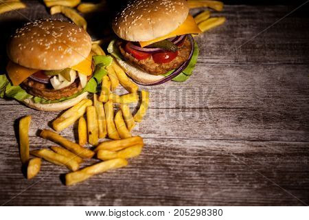 Delicious tasty burgers on wooden background. Fast and tasty food