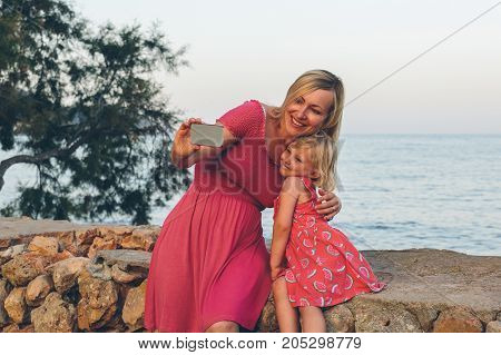 Mother and daughter taking a selfie with a mobile phone in front of the sea.