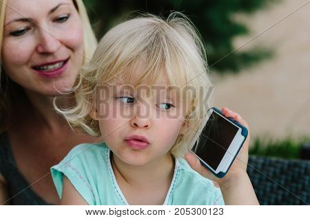 Little blond girl sitting on her mom's lap and playing with a smartphone.