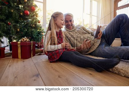 Indoor shot of senior man with his granddaughter using digital tablet at home during Christmas. Mature man lying on floor holding tablet pc with his granddaughter sitting by.