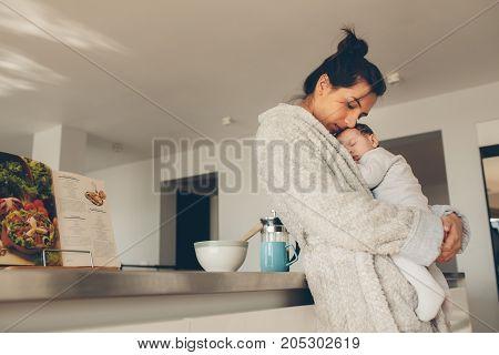 Loving Mother Carrying Her Newborn Boy In Kitchen