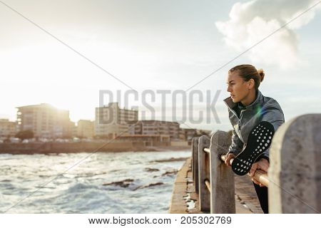 Healthy Woman Stretching On Railing At Seaside Road
