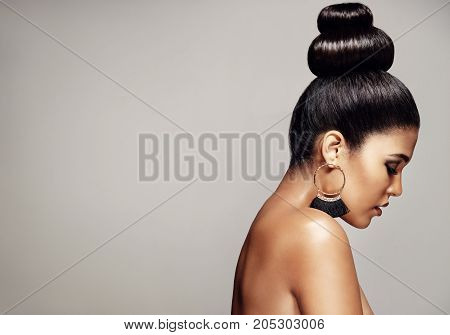 Side view of woman with elegant hairstyle and makeup against grey background. Female model topless in studio with copy space.