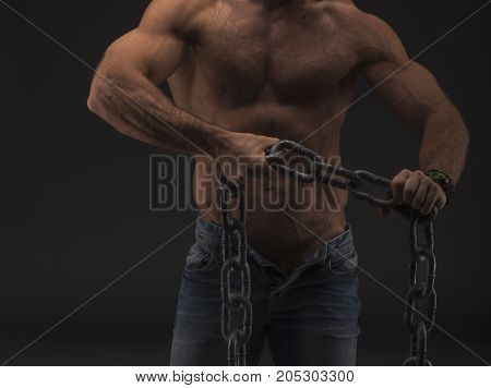 Muscular Sexy Man With Big Chain Only In Jeans. Strong Nude Male Body With Veins