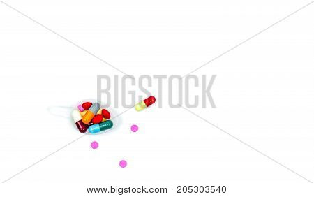 Colorful of tablets and capsules pills in plastic teaspoon and some of them spread on white background with copy space just add your own text.