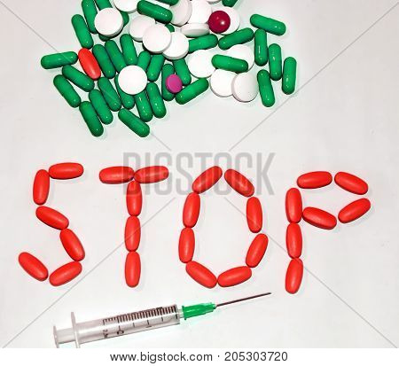 Tablets and capsules are laid out the word Stop. Syringes.