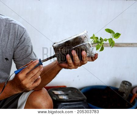 Man drilling plastic glass to keep the water running for plant