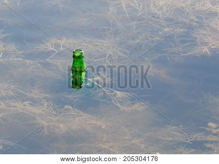 bottle of water in the lake . In a park in the nature