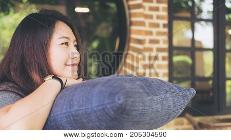 A beautiful Asian woman sit with chin resting on her hands above a blue pillow with feeling happy and relax in cafe bricks wall and nature background